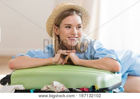 Smiling Young Blonde Woman In Hat Packing Suitcase And Looking Away, Packing Luggage Concept