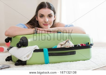 Beautiful Young Brunette Woman Packing Suitcase And Looking At Camera, Packing Luggage Concept