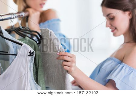 Smiling young women choosing clothes together indoors