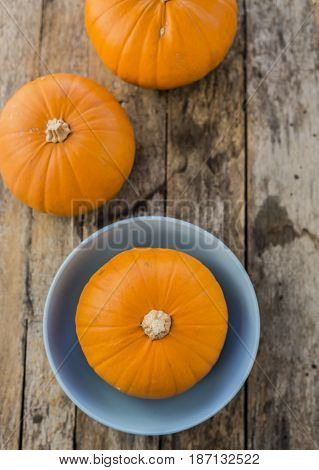 three pumpkins on wooden background close up