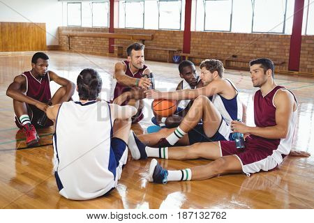 Basketball players interacting while relaxing in the court