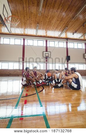 Smiling basketball players interacting while relaxing in the court
