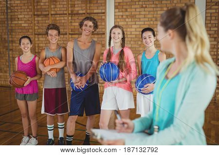 Smiling coach talking to high school kids in basketball court
