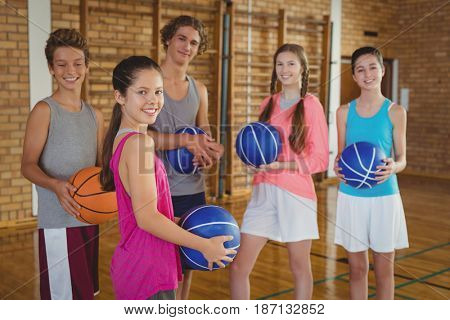 Portrait of high school kids holding basketball together in the court