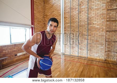 Determined basketball player holding basketball in the court