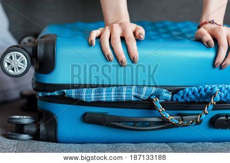 Human Hands Holding Overloaded Suitcase With Wheels On Sofa, Packing Luggage