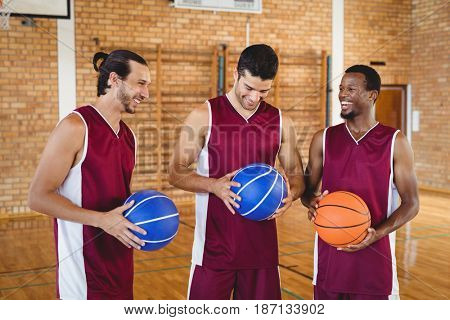 Smiling basketball players interacting with each other in the court