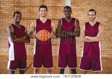 Portrait of confident basketball players holding basketball in court