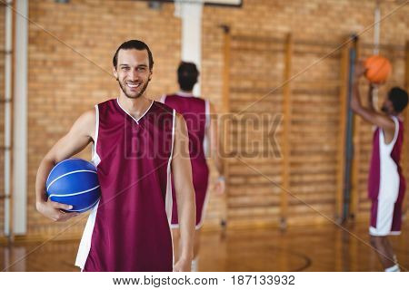 Portrait of smiling basketball player holding a basketball in the court
