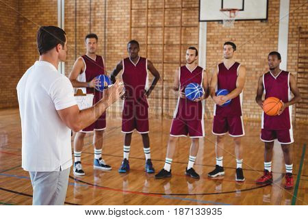 Basketball coach interacting with players in the court
