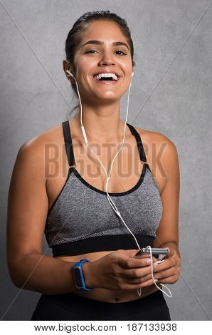 Cheerful young woman having fun while listening to music. Fit girl holding mp3 player enjoying music after workout. Happy smiling athlete listening to music.