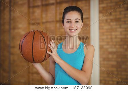 Portrait of smiling girl holding a basketball in the court
