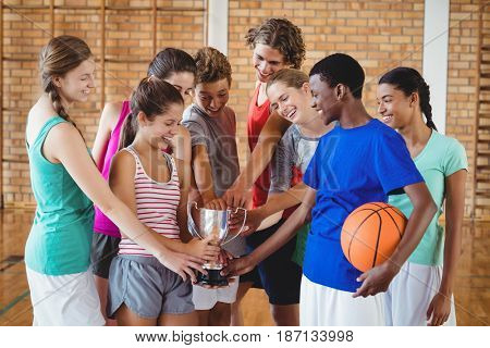 Portrait of excited high school kids holding trophy in basketball court