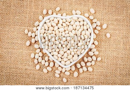 White beans seeds in whtie dish on burlap background.