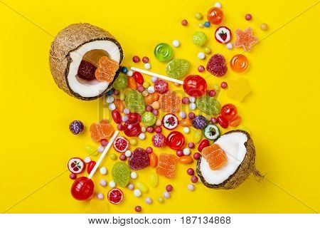 Colorful explosion of candies in coconut on yellow colored background creative still life flat lay style