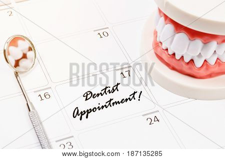 Dentist appointment word on calendar page and Dentist mirror tool and dentist demonstration teeth model.