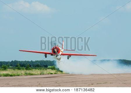 Zhitomir Ukraine - June 17 2011: Yakovlev Yak-52 aerobatic plane passing low over the runway