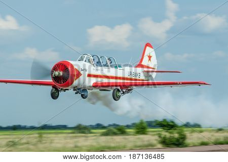 Zhitomir Ukraine - June 17 2011: Yakovlev Yak-52 aerobatic plane passing low on sumemr day