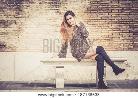 Beautiful and attractive young woman sitting on a bench in the street. The woman is smiling with sensual attitude. Behind her a brick wall.
