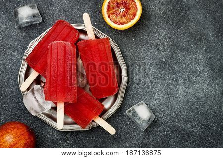 Homemade frozen blood orange natural juice alcoholic popsicles - paletas - ice pops. Overhead flat lay top view copy space
