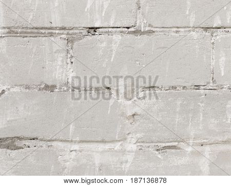 White bricks wall background. Retro building texture - bricks with aged white paint stains.  Construction wallpaper with empty place for text. Closeup view.