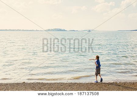 boy throws stones at the seashore. child is looking at a floating boat. Copy space for your text