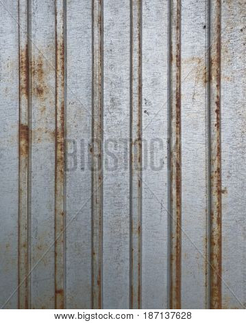 Grunge gray rusty metal fence texture. Aged steel background with vertical structure. Real iron plate with stripes. Industrial wallpaper.