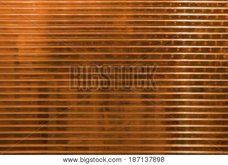 Orange polycarbonate surface with  objects behind.  Industrial background, regular structure with horizontal structure. Plastic texture with place for text.