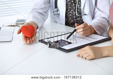Doctor heart and patient. Physician discussing health exam with future mother. Medicine, healthcare and pregnancy concept.