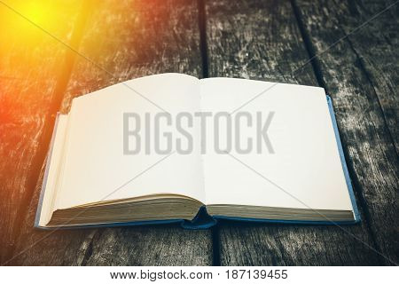 Old open book on a wooden table. Vintage composition. Ancient library. Antique literature. Fabulous atmosphere. Medieval and mystical background retro style religion. Close up view.