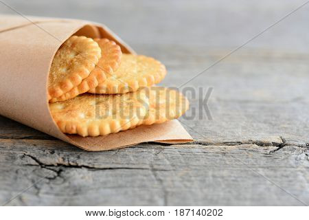 Salty round crackers in a wrapping paper on a vintage wooden background with copy space for text. Delicious crackers snack idea for kids or adults