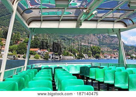 View inside ferry boat with green seats. Como lake Italy.