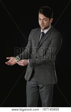 Young Businessman With Dollar Banknotes In Sleeve Isolated On Black