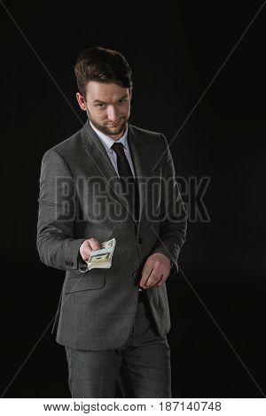 Young Sly Businessman Giving Dollar Banknotes Isolated On Black