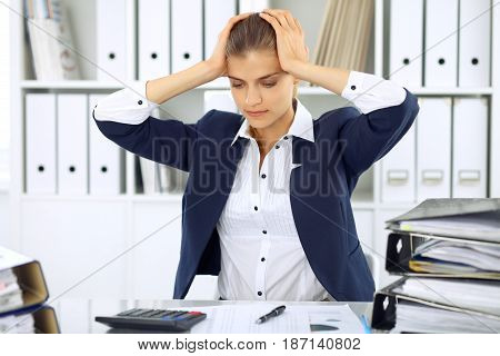 Tired business woman or female accountant with bills and paper folders in office.