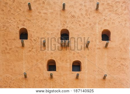 African adobe wall structure with beams and windows. Background