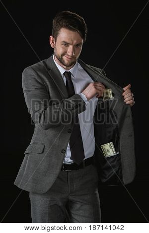 Young Sly Businessman With Dollar Banknotes In Pockets Isolated On Black