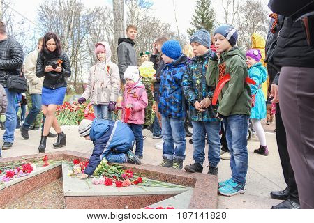 Kirishi, Russia - 9 May, Children at the monument to the fallen in the war, 9 May, 2017. Laying wreaths and flowers in memory of the fallen at the Eternal Flame.