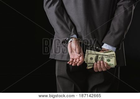 Partial View Of Businessman In Handcuffs Holding Money Isolated On Black, Corruption Concept