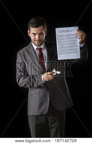 Cunning Businessman Holding Contract And Cigarette Lighter Isolated On Black
