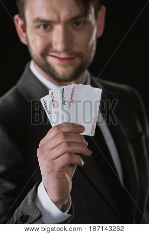Businessman Holding Joker Cards In Hand Isolated On Black, Focus On Foreground