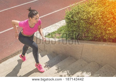 Muscular sportswoman running up on stairs. Morning workout. Urban scene. Fitness sport recreation workout healthy lifestyle concepts.