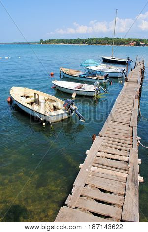 Five small boats attachted to a wooden pier