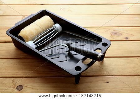 Paint Roller and Tray on Wooden Background