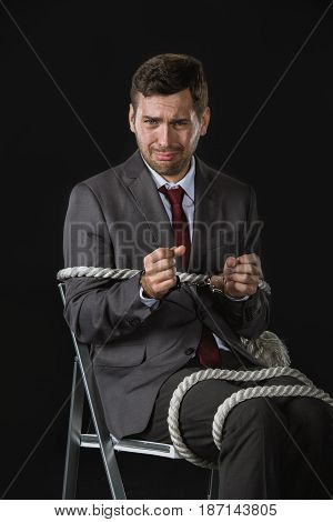 Young Upset Businessman Roped On To Chair Isolated On Black