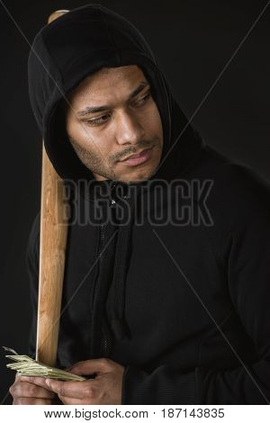Young Robber In Zoodie With Baseball Bat And Money Isolated On Black