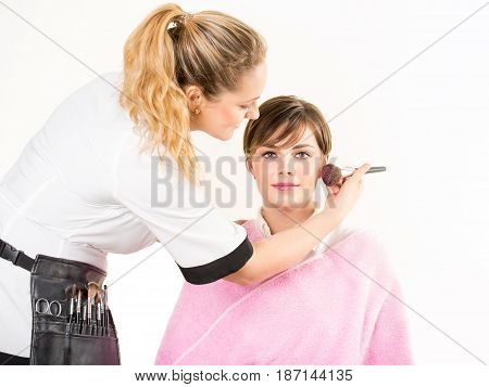 Beautician Applying Blusher To A Young Woman
