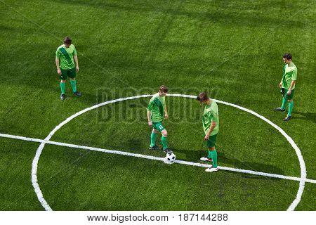 Thq legs of soccer football player training football on green grass field