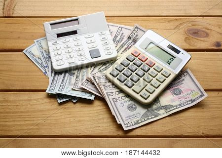 Calculator and Bank Notes with Wooden Background