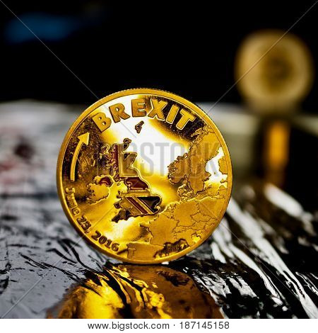 Europe leaving. Gold brexit physical coin in black scene